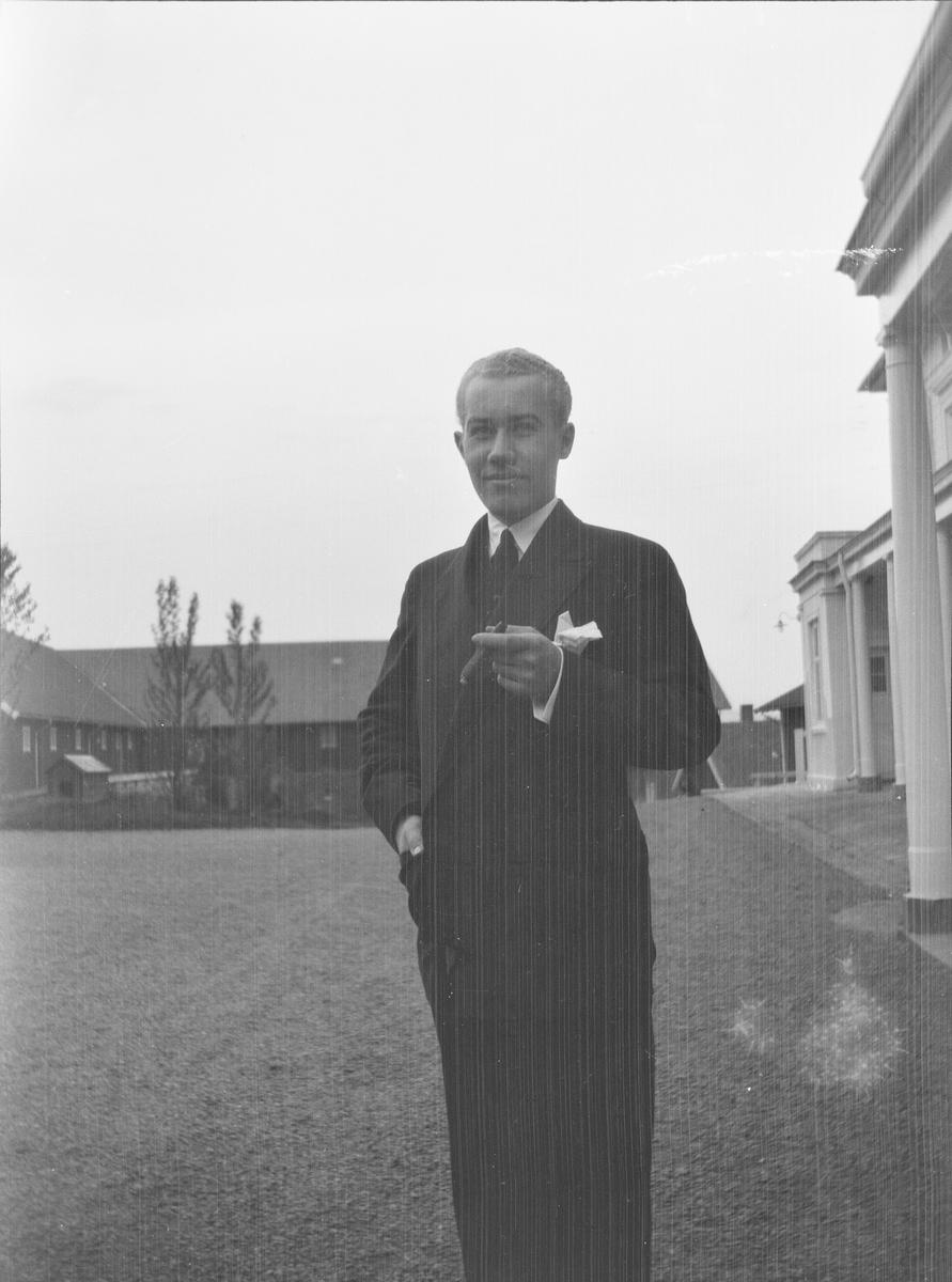 Iacob Ihlen Mathiesen står på gårdsplassen utenfor hovedhuset på Linderud Gård med en sigar i hånden. I bakgrunnen sees driftsbygninger tilhørende gården.