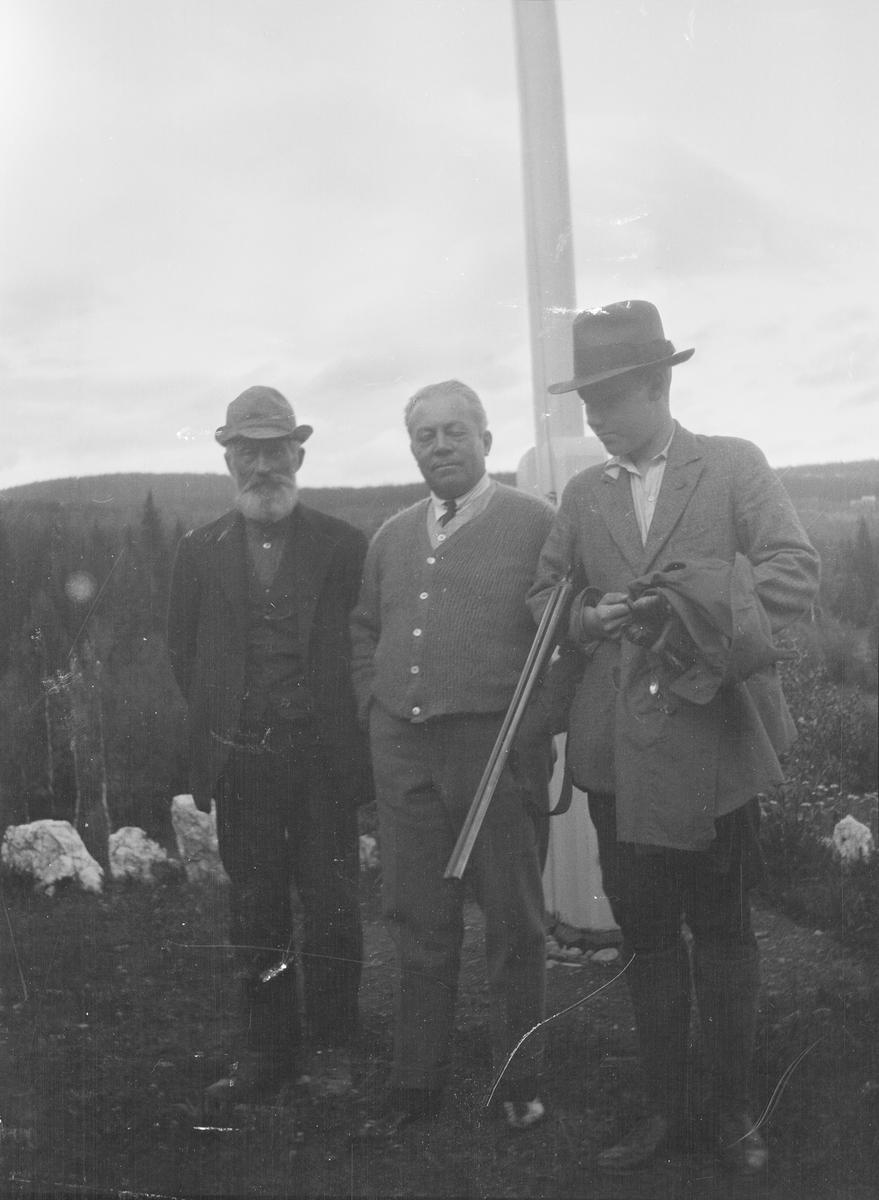 Tre menn står sammen ved en flaggstang. I bakgrunnen ser man utover et skogkledt åslandskap. Mannen i midten er Christian Pierre Mathiesen og den yngste mannen med knekt hagle under armen er hans sønn Iacob Ihlen Mathiesen. Den tredje mannen er uidentifisert. Antakelig er bildet tatt i Jeppedalen.