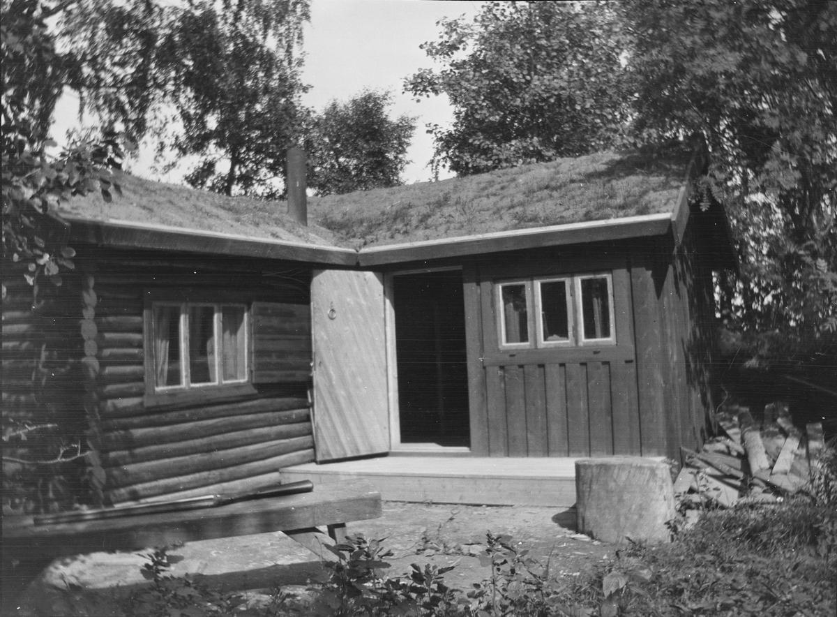 Et bilde av en tømmerhytte i en løvskog, sannsynligvis også brukt som jakthytte. Døren til hytta står åpen. Planker ligger ved en hyttevegg. En hagle ligger på et bord som står foran hytta. Foran hytta står det også en stubbe.