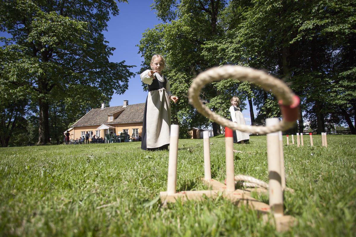Jenter i gammeldagse kostymer leker med ringspill på plenen utenfor museet.