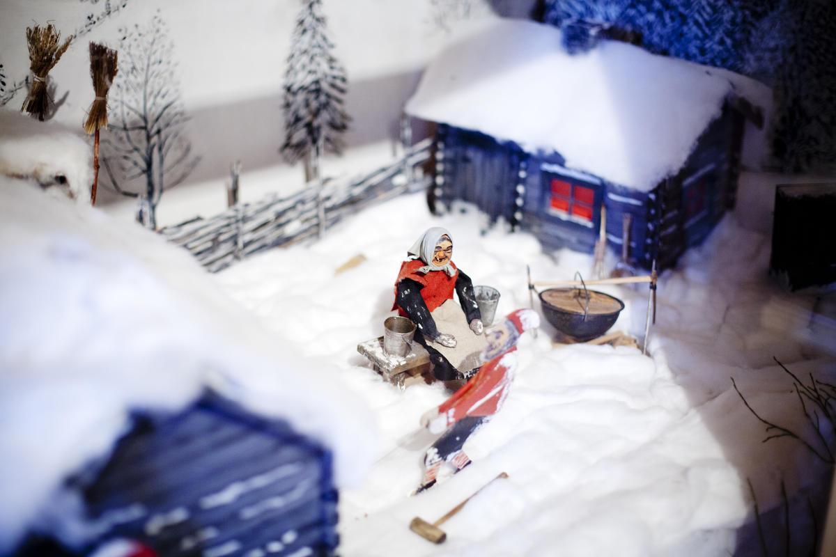Mekanisk juleutstilling med figurer nissefar og nissemor utenfor et hus.