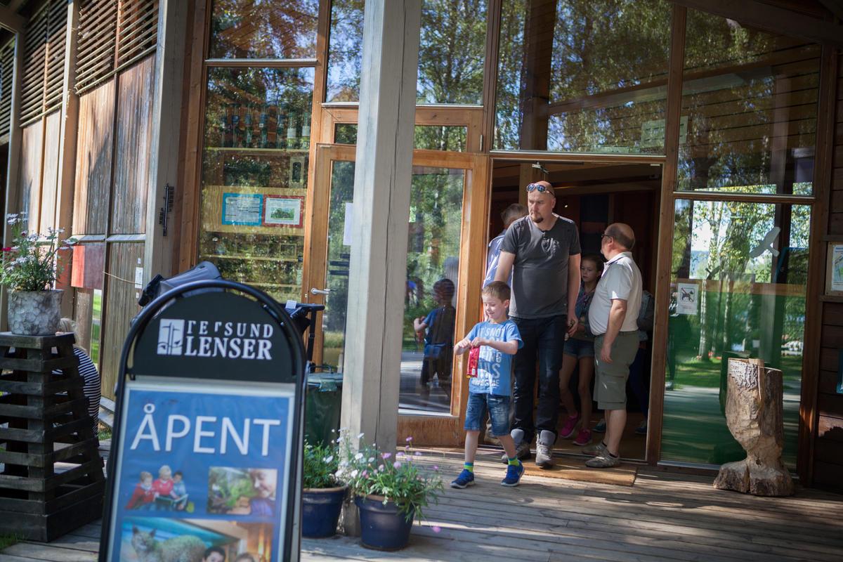 Foto av familie utenfor inngangspartiet til besøkssenteret (Foto/Photo)