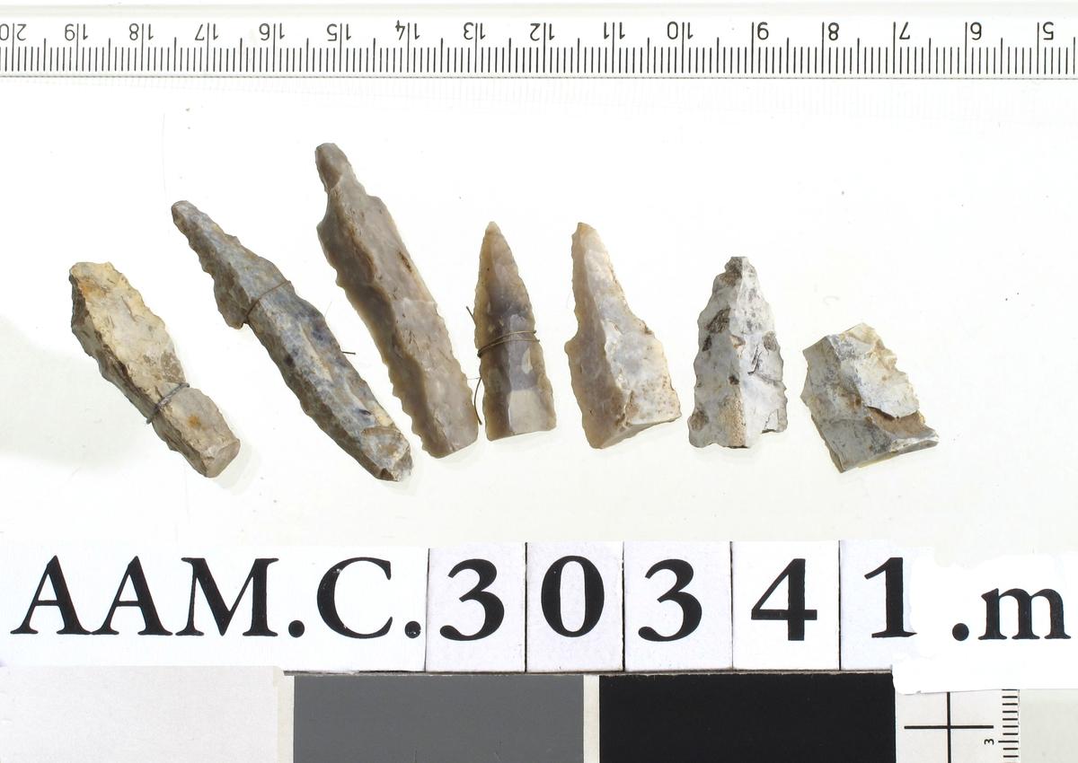 7 fragmenter av tresidige pilespisser av grålig ogmelkehvit flint, av typen H. Gjessing: Rogalands Stenalder, fig. 174.   Lengde 2-5,3 cm   (A. 1772 a, 1785, 1870 a, 2209, 2211).