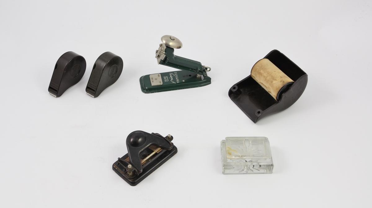 Seks kontorrekvisitter: to tapedispensere, en stiftemaskin, en hullemaskin, en papirdispenser og en frimerkedispenser.