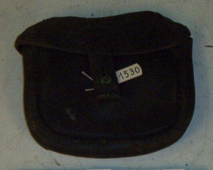 Tasken har bærestropp, lokk med lærhempe og hvit metallknapp. Utlånt fra Forsvaret i forbindelse med anskaffelse av lærtøy og en del annet utstyr til Utrykkningspolitiet.