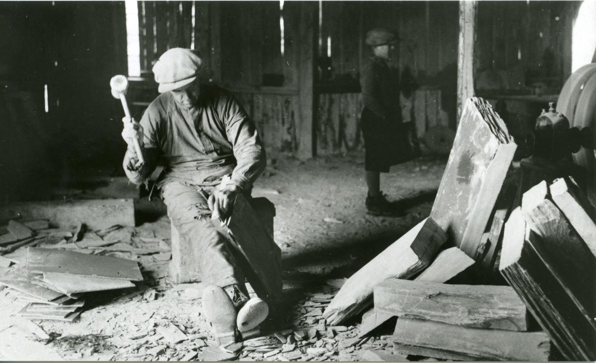 En mann i arbeidsklær sitter og kløyver stein ved Valdres skiferbrud. I bakgrunnen står en yngre gutt.
