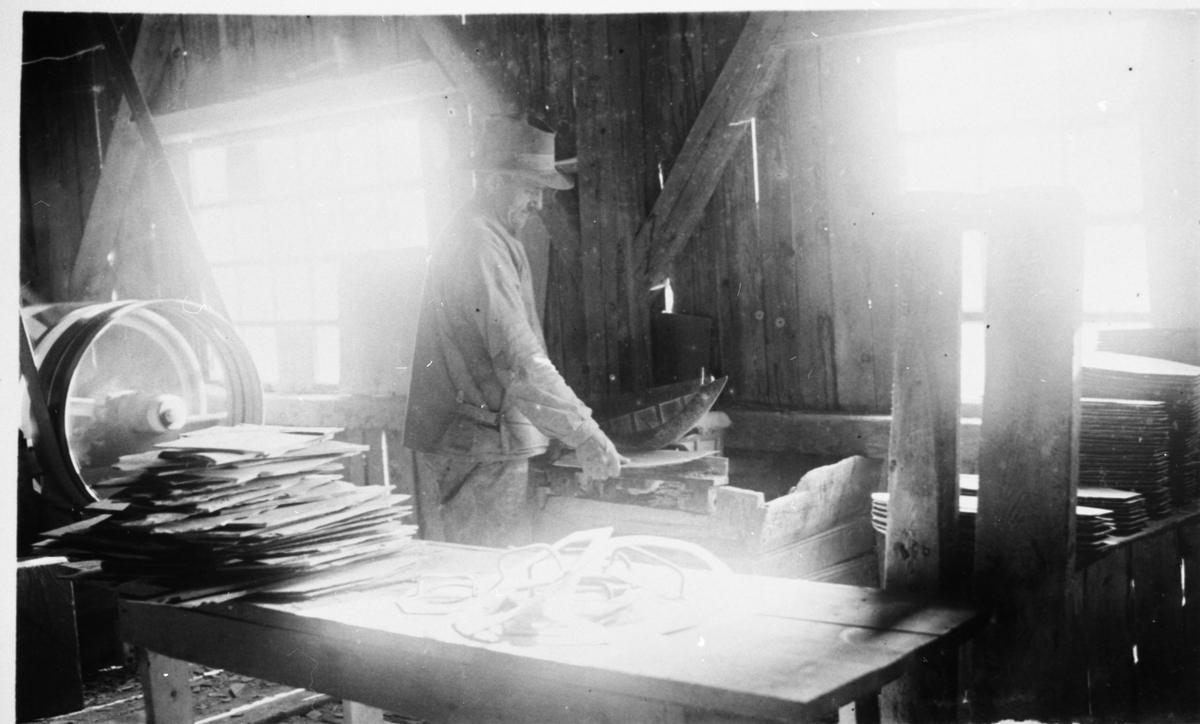 En mann kapper stein ved Valdres Skiferbrud. Mannen er iført arbeidsklær og hatt.