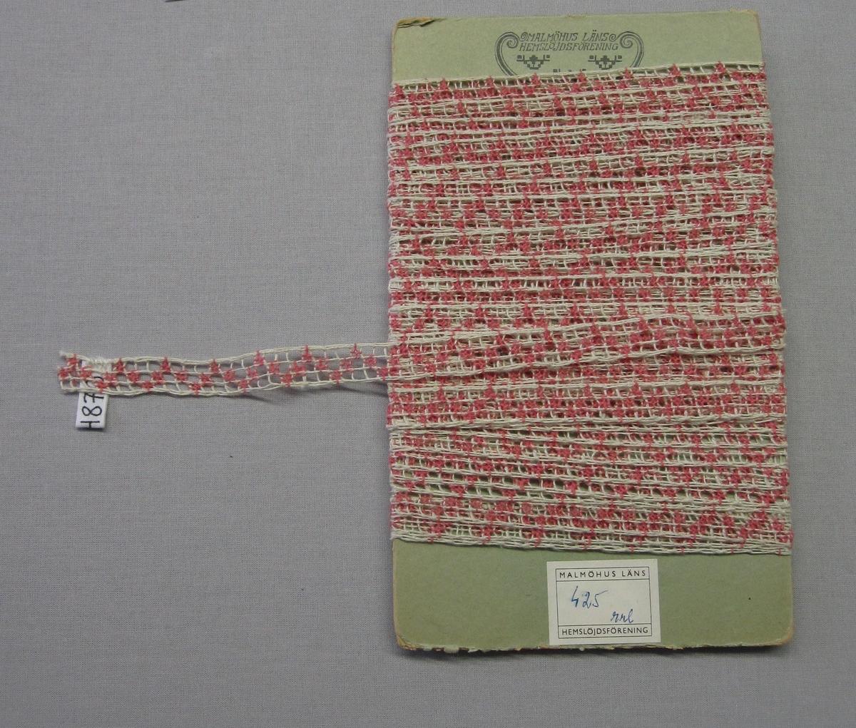 """Smal filéknuten spets med trätt mönster, knutet och trätt. Nätet är knutet av rakställda rutor i halvblekt lingarn. Glest trädda singlingar i rosa bomullsgarn bildar ett sick-sackmönster. Spetsen som sålts som metervara är lindad på kartong stämplad """"MALMÖHUS LÄNS HEMSLÖJDSFÖRENING"""" och med prislapp märkt: """"4.25  rrl""""."""