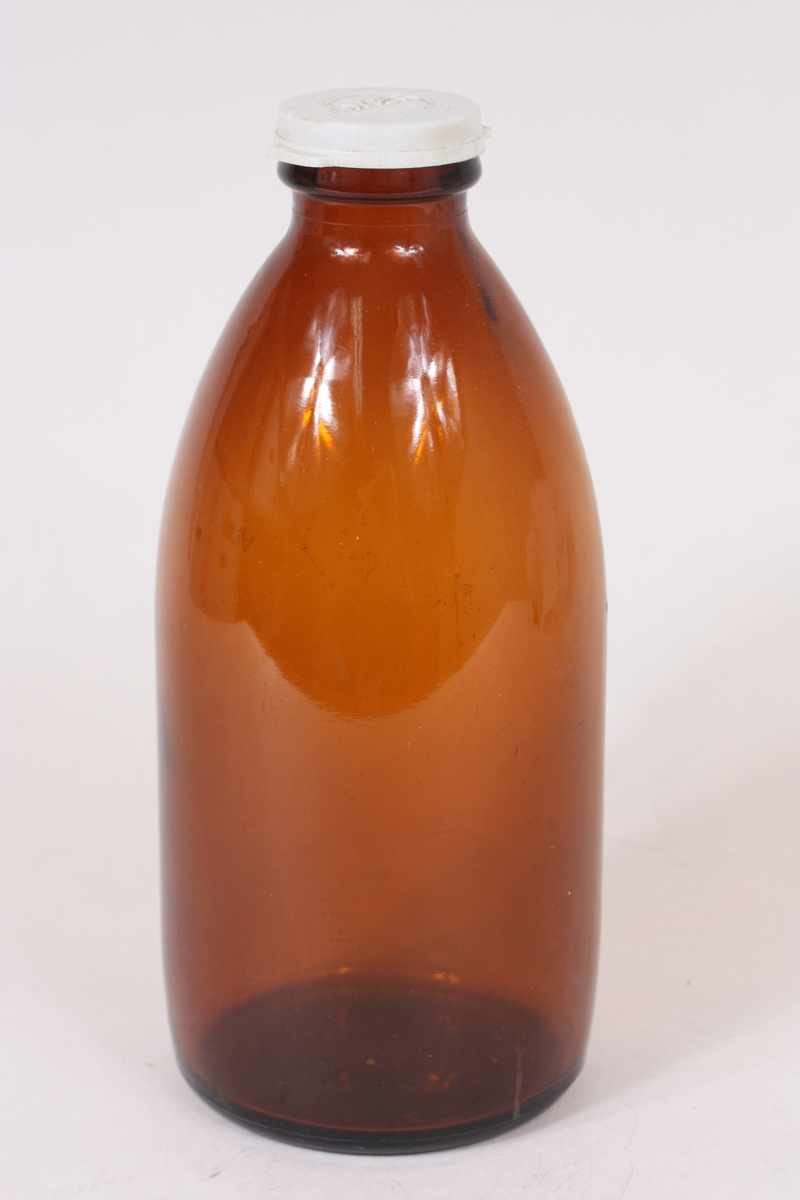 Form: sylinderisk, med avrunda topp og liten tut. Plastkork