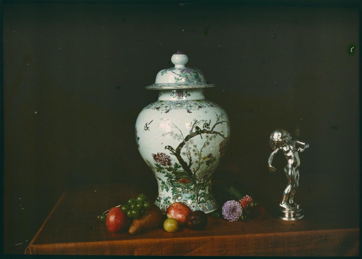 Autokrom.Stilleben: Urna, statyett, frukt och blommor.