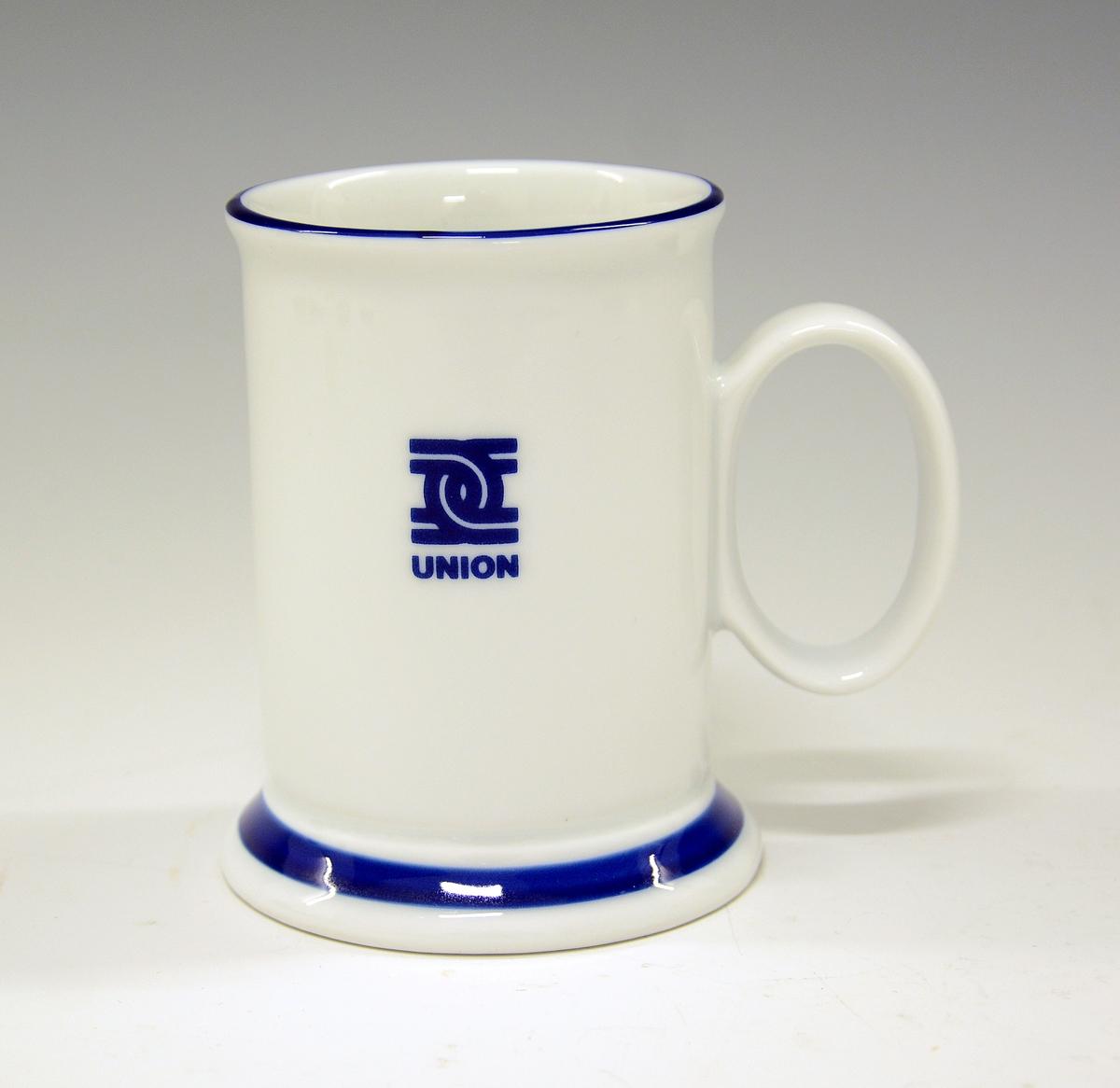 Krus i porselen. Med støpt fot. Hvit glasur. Blå kanter og logoen til papirfabrikken Union, Skien. Modell av Eystein Sandnes.