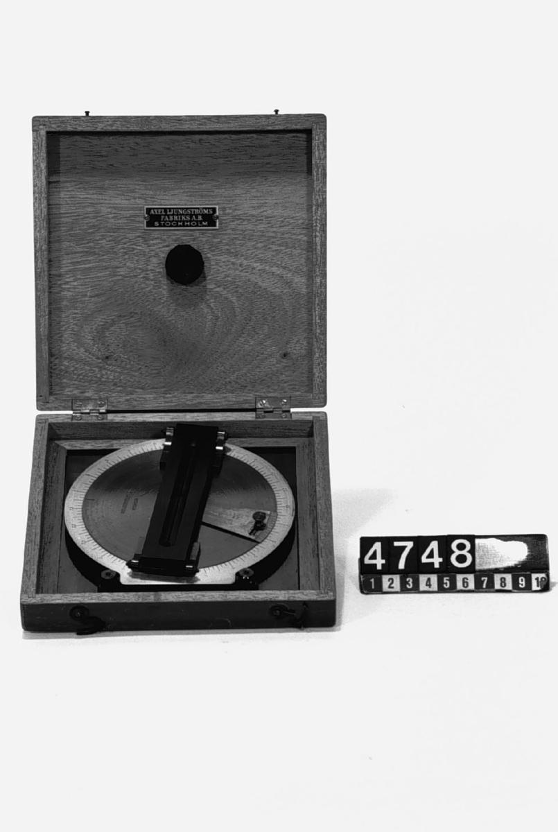 """Vinkelavläsningsinstrument för att orientera ett mätbord vid kartläggning med distanstub. Märkt: """"Axel Ljungströms FAB Stockholm"""". Tillbehör: Förvaringslåda av trä."""