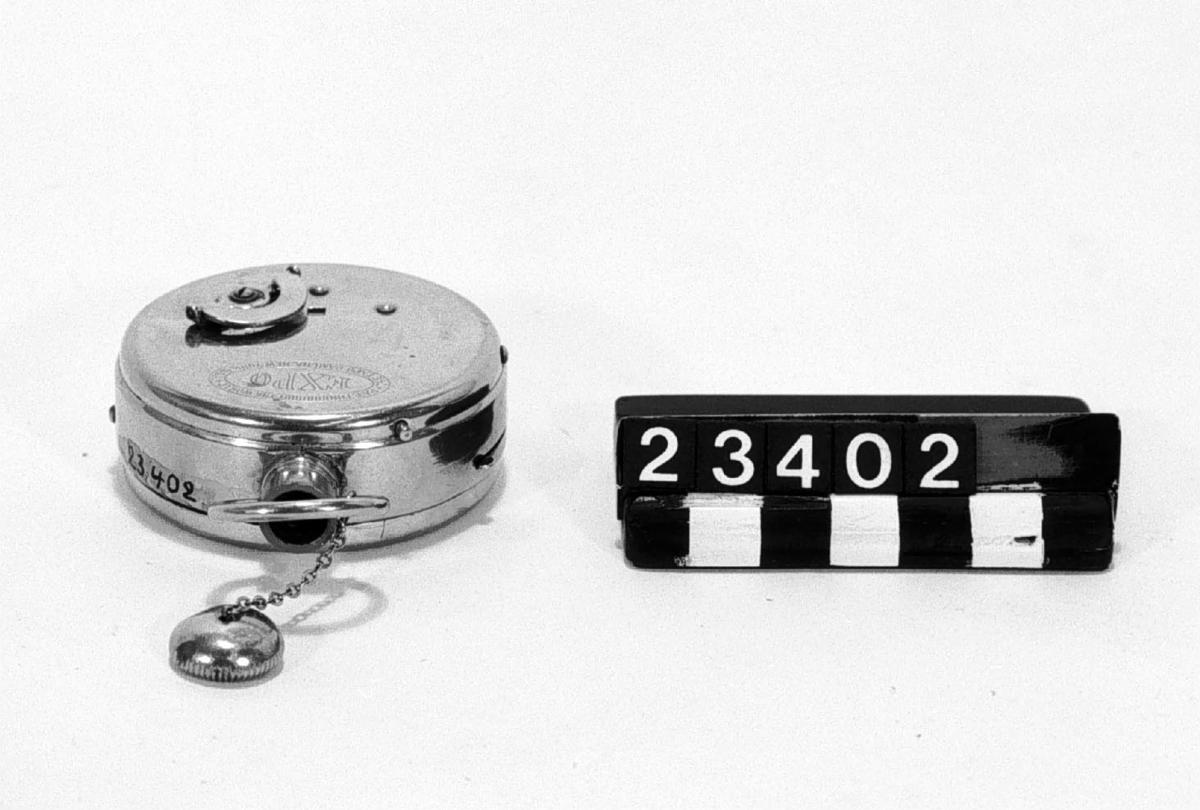 """Kamera i form av fickur """"Expo watch camera"""", för rullfilm i specialkassett. Objektivet, en enkel lins, i remontoaröppningen. I kamerans främre del saknas en halvcirkelformad skiva av 2 mm tjock röd fibermassa med tryckt text: EXPO (vitt) pat. througout the world U.S. patent sept. 6. 1904. Denna skiva är på T.M. kopierad 14/4 -62 efter en annan kamera (tillh. Herr Werneström, Sthlm) som dessutom hade ett fodral av ljusbrunt läder. Tillbehör: Tom filmkassett."""