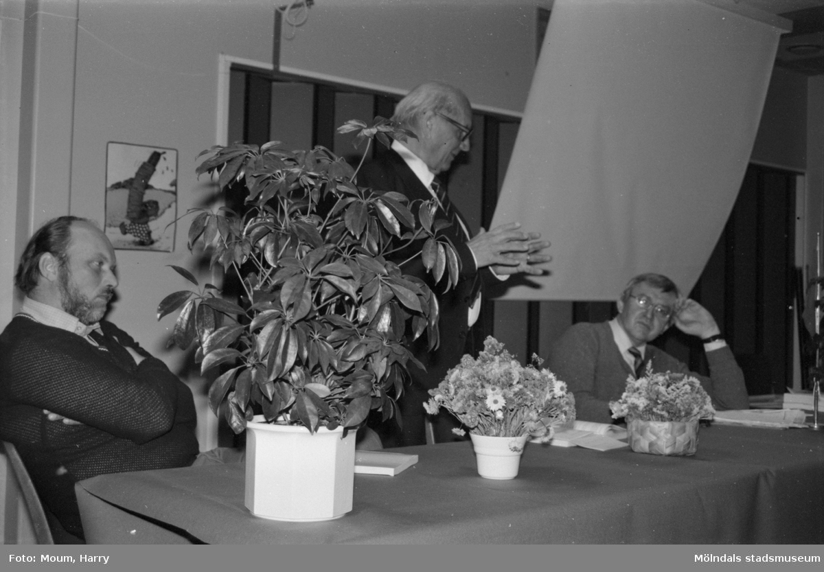 """Centern anordnar en informations- och diskussionskväll om miljö och naturens resurser på Rävekärrsskolan i Mölndal, år 1984. """"Nils Dahlbeck, som ett helt liv har arbetat för bra miljö och livskvalitet förklarar problemen med den globala miljöförstörelsen för Erik Arrhenius, Jimmy Stigh och en stor skara åhörare.""""  För mer information om bilden se under tilläggsinformation."""