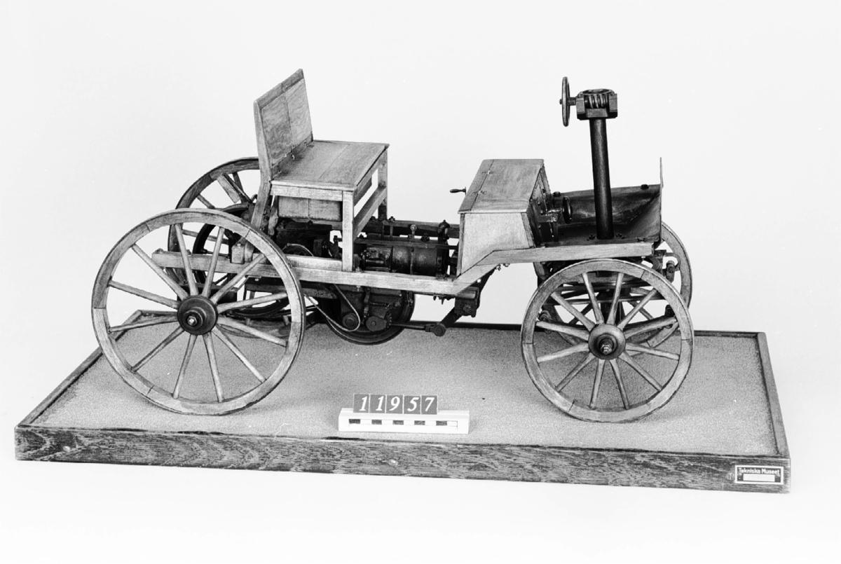 Modell i skala 1:5 av bensinmotordriven bil med hästvagnsliknande kaross. Motorn tillverkad av Märky, Bromovsky & Schultz 1888. Kraftöverföring från motorn med remmar till remskiva på bakaxeln. Ram av trä, framvagn med halvelliptiska fjädrar. Trähjul skodda med järnband. Förebilden har 2 m axelavstånd. Monterad på en platta 700 x 400 mm  Encylindrig luftkyld fyrtaktsmotor Effekt cirka 4 hk