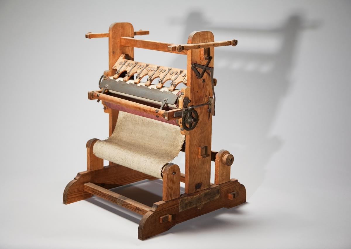 """Modell av överskärningmaskin. Text på föremålet: """"N:o 206. Modell på öfverskäraremachin i anledning av Hr Comercie Rådet Polhems .... förbättrad af Commissarien Norberg. C-e-26 Överskärnings-maskin-av Polhem förbättrad av Norberg"""". I Jonas Norbergs förteckning från 1779 beskrivs modellen på följande sätt: """"Modell på Öfverskjärare Machine i anledning av förutgående, men med åtskillige hufvudsaklige förändringar. Häraf äro Modeller begärde och skickade till England och Danmark."""""""
