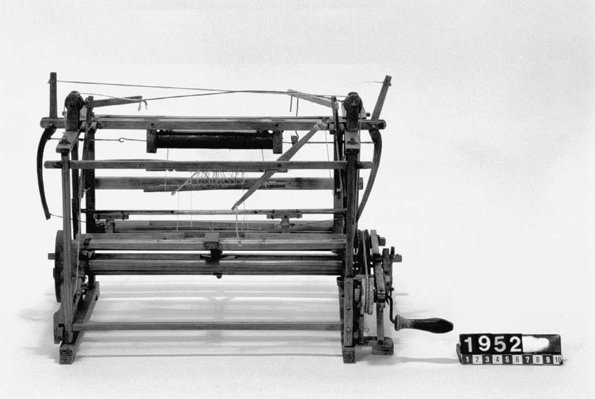 """Modell av vävstol. Text på föremålet: """"XVII.D.11. C.G. Nyström""""."""