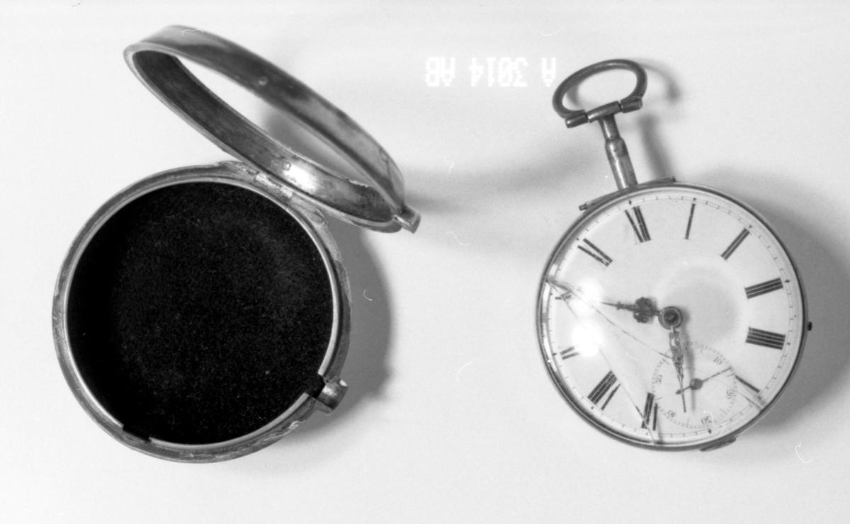 .A: Ur. Baksiden av sølv, hvelvet glass. Tallskive med romertall, sekundtallskive, ring.B: Hylster. Sirkelformet, hvelvet bunn med hakk til holder i overkant. På oversiden hvelvet ring påsatt hengsel