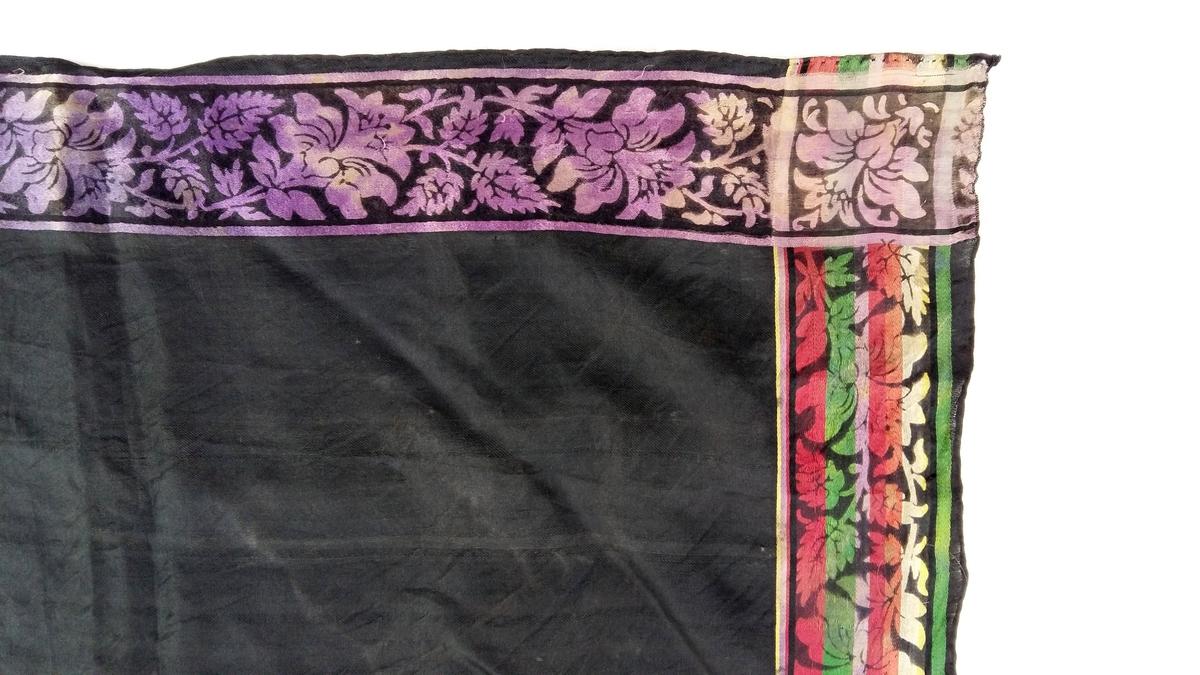 Langs sidene blomsterfriser avbrotne av hjørnekvadrat med skråstilt blomster. Mot det svarte er i frisane 2 møtande sider fiolett, dei 2 andre stripa i fleire fargar.