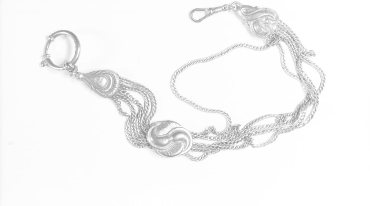5 lenker i begge ender, på midten et stykke med støpt dekor og uregelmessig ytterkontur. I den ene enden en ring, i den andre en pæreformet krok.