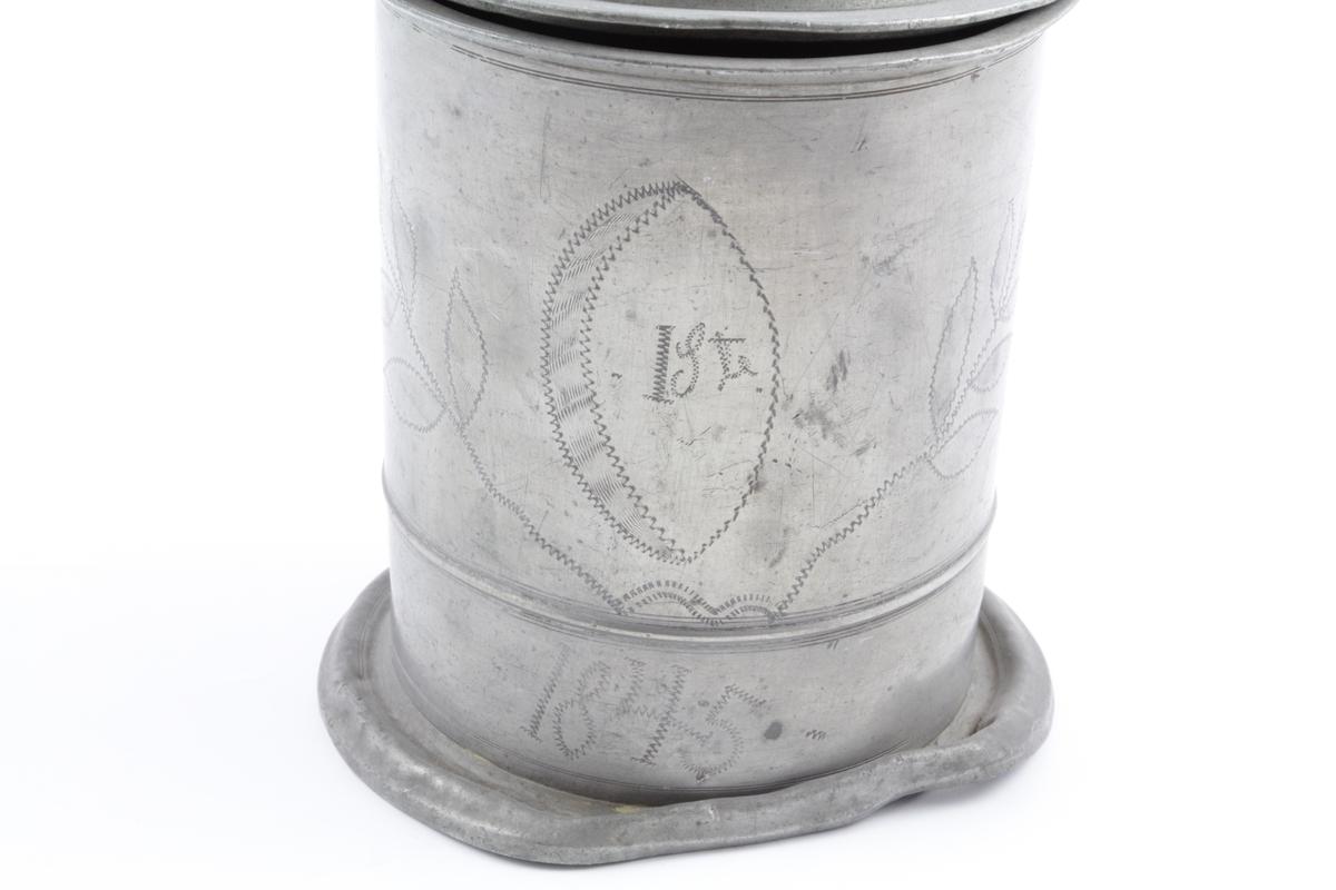 """Profilbilde av """"Carolus XIV Joh. Rex Sveciae et Norvegiae"""" på kannens lokk. Blomstergrener, tall og bokstaver er gravert inn på kannens korpus."""