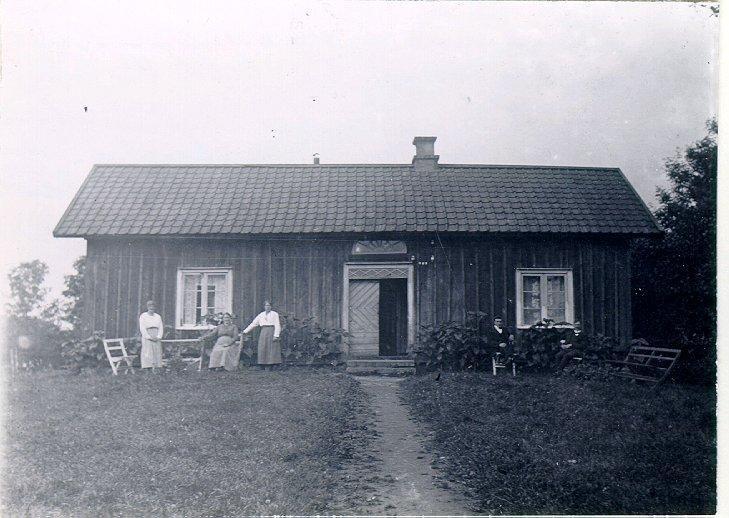 Segerstads sn. Pickagården. Ägare John Eriksson längst till höger om dörren, närmare denna systersonen Garfild Bohlin. På andra sidan dörren systerdottern Nelly Bohlin och dennes moder Vilhelmina Bohlin  i granngården med samma namn sittande samt systerdottern Elin Svenningsson längst till vänster.
