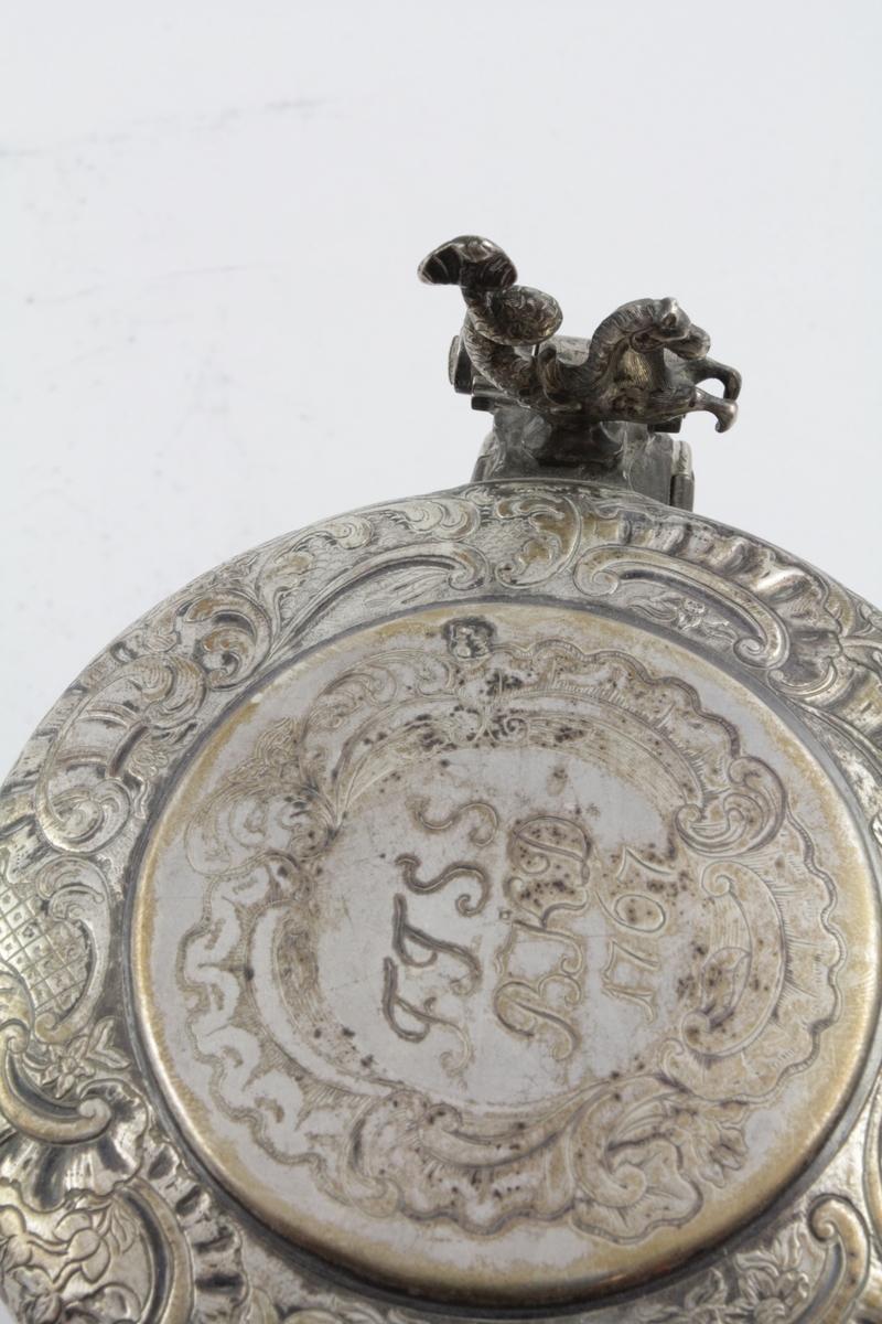 Leirtøy, sort, syllindrisk, glassert. Sylindrisk med horisontale riller øverst og nederst. Sølvlokk hvor kanten er prydet med drevne c-ornamenter, rocailler, blad og blomster. Midtpartiet har lignende ornamenter, men graverte. Lokkåpneren er utformet med hode og forpart av en hest.