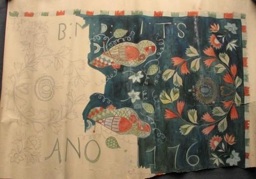 """Skiss målad på kraftigt papper. Hel agedyna. Drygt hälften är färglagd. I mitten två papegojor, liggande vända mot varandra. Var sida om papegojorna stor krans med granatäpple i mitten. I hörnen mindre blombukett. Monogram BMD, ITS, ANO 1776. Mörkblå botten. Kavelfrans runt om. Gammal märkning på baksidan: """"Gärds h-d  Nr.3, KLH Z2:618,  (No 213 KLH) (Z 1372)  se i Gärds."""