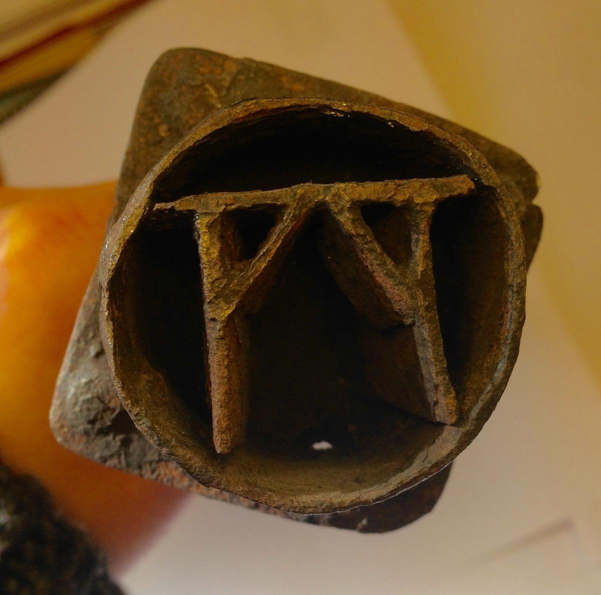 Sirkelformet brennjern med galgesymbol. Brennjernet er festet til fire stag som er smidd sammen til en tange påmontert et dreiet treskaft med holk.