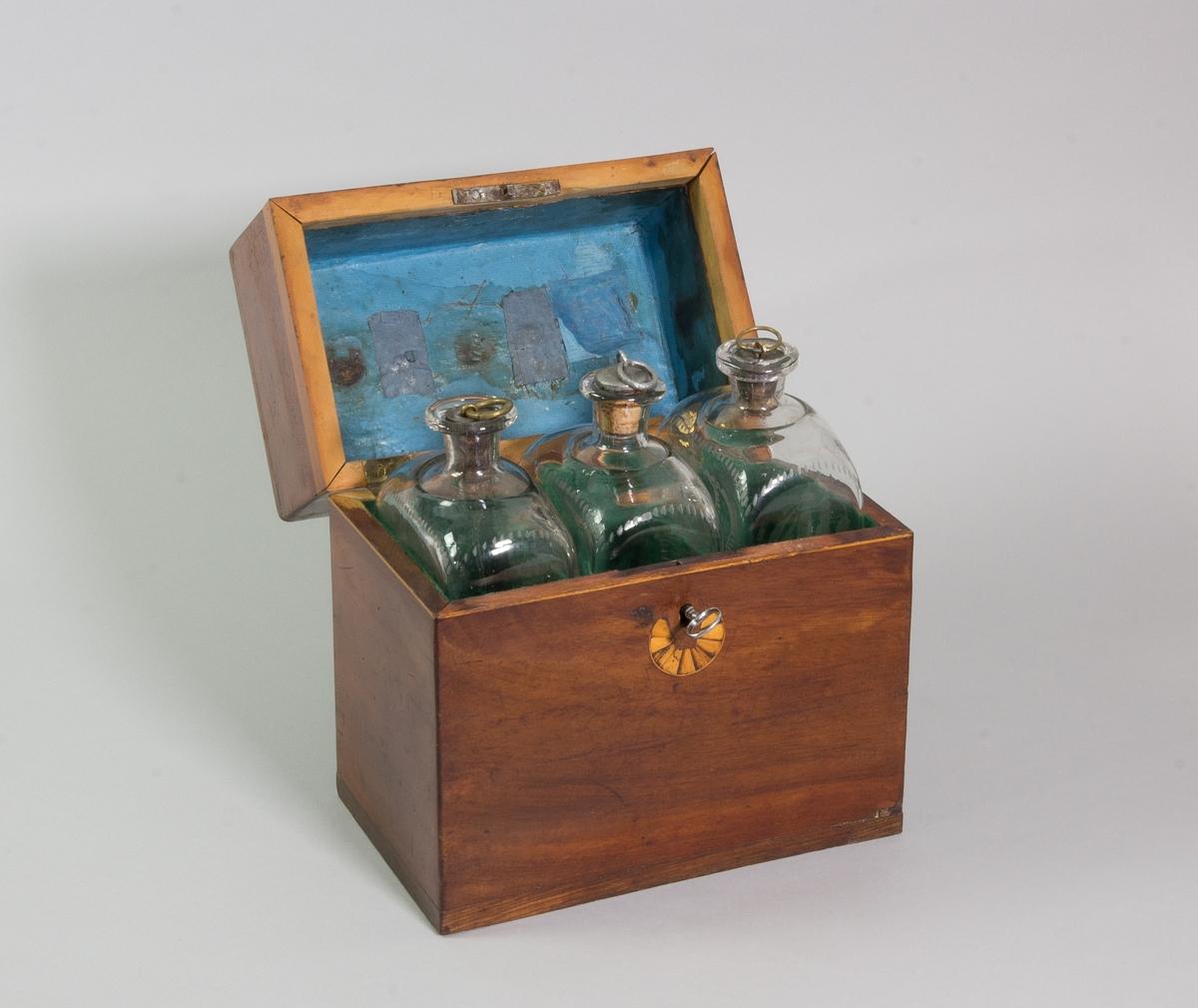 Flaskschatull av mahogny innehållandes tre brännvinsflaskor av klart ofärgat glas med graverad dekor.