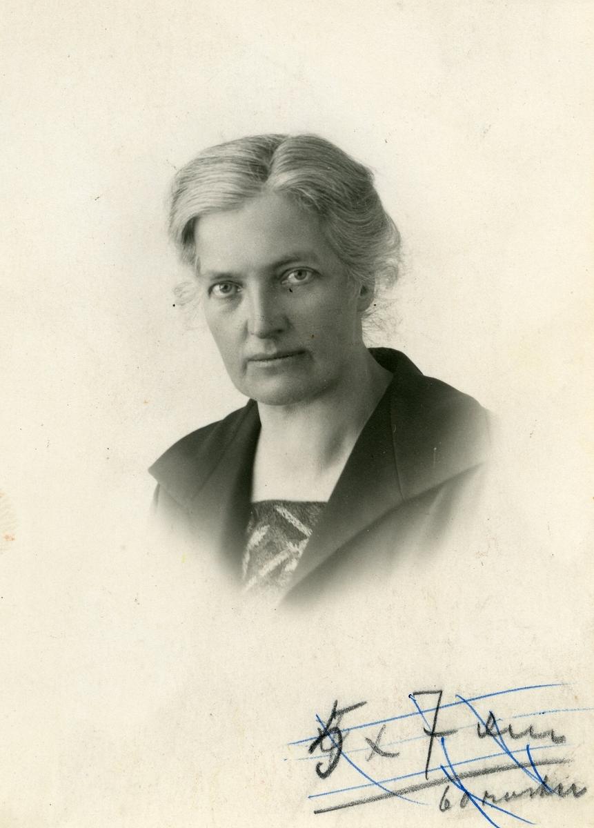 Portrett av en kvinne. Kvinnen er iført jakke med store slag med en bluse eller kjole under. Håret er satt opp.