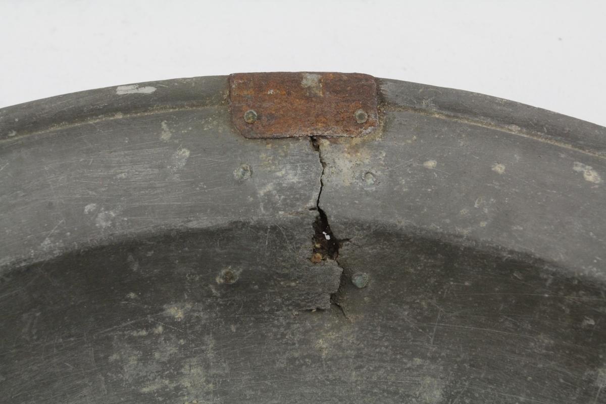 Ganske sterkt fordypet midte, kanten oppadskrående med inngravert linje ved randen. Sprekk i kanten reparert med pånaglet skjøt av metall.