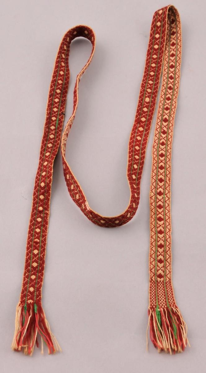 Grindvove band med frynser i begge endar. I eine enden  har bandet annan mønstring dei to siste cm før frynsene.