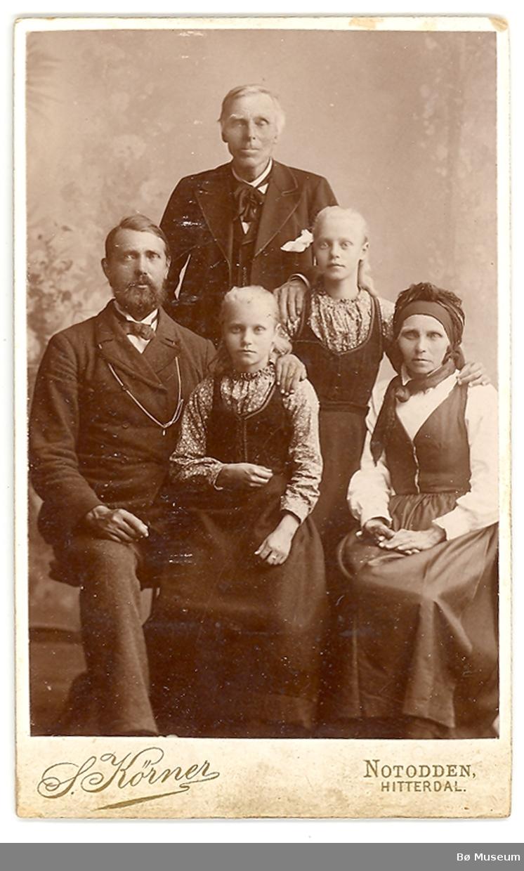 Familiegruppe på fem i fotoatelier. På bildet sitter ekteparet Knut T. Haugestul og Gunhild Jørgensdtr. t.v. og h. Tvillingdøtrene Åste t.v. og Guro t.h. Bror til Gunhild, Guttorm J. Firingen, står bak.