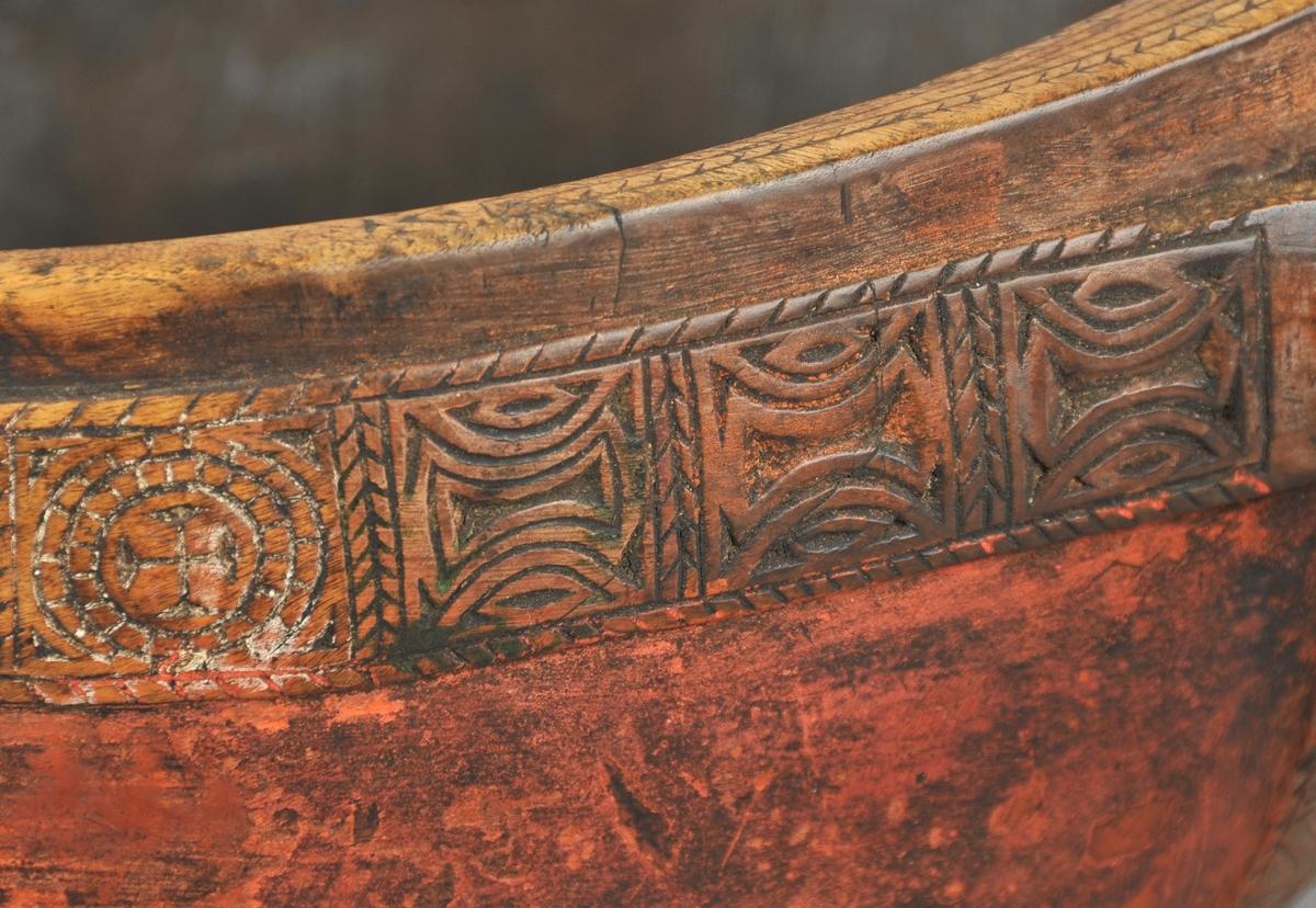 Trøys som er uthola frå ein bjørkenut. Oval i forma. Under botnen og på baksida av handtaket  er det  svidd inn bumerke. Trøysa er måla med rød og brun farge.  Utskjæringar langs kanten. På tuten, som er femkanta, er det utskorne halvsirklar og firkantar. Handtaket er utforma som ein vifteforma hale. Frå baksida av handtaket og ned mot botnen går det eit breidt, utskore band i kors og strekornamentikk.