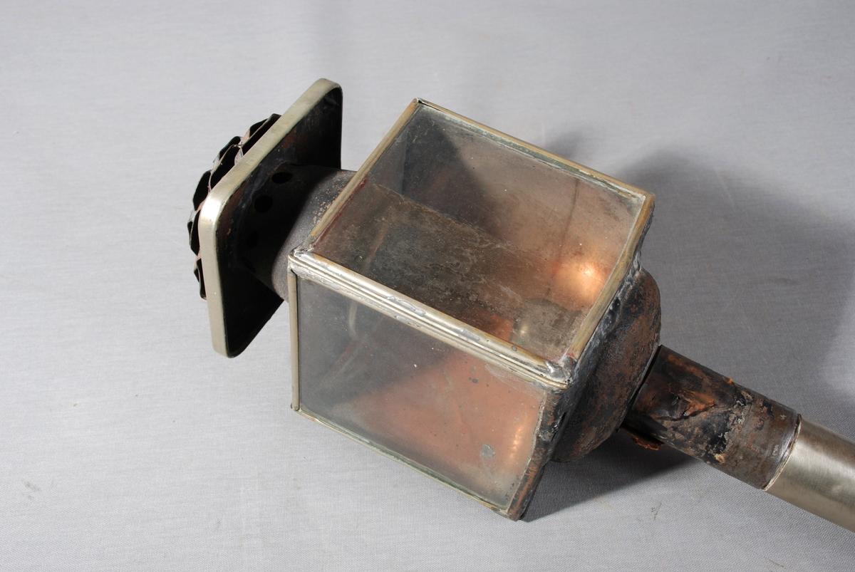 Olje-/stearinlyslykt til bruk på hestevogn eller slede. Firkantet lyktehode på metallrør. Øverst hatt for utlufting. Lyktehodet kan åpnes ved at ene siden av metall er hengslet. En side er av rent metall og to sider er av glass. Innvendig base for brenner.