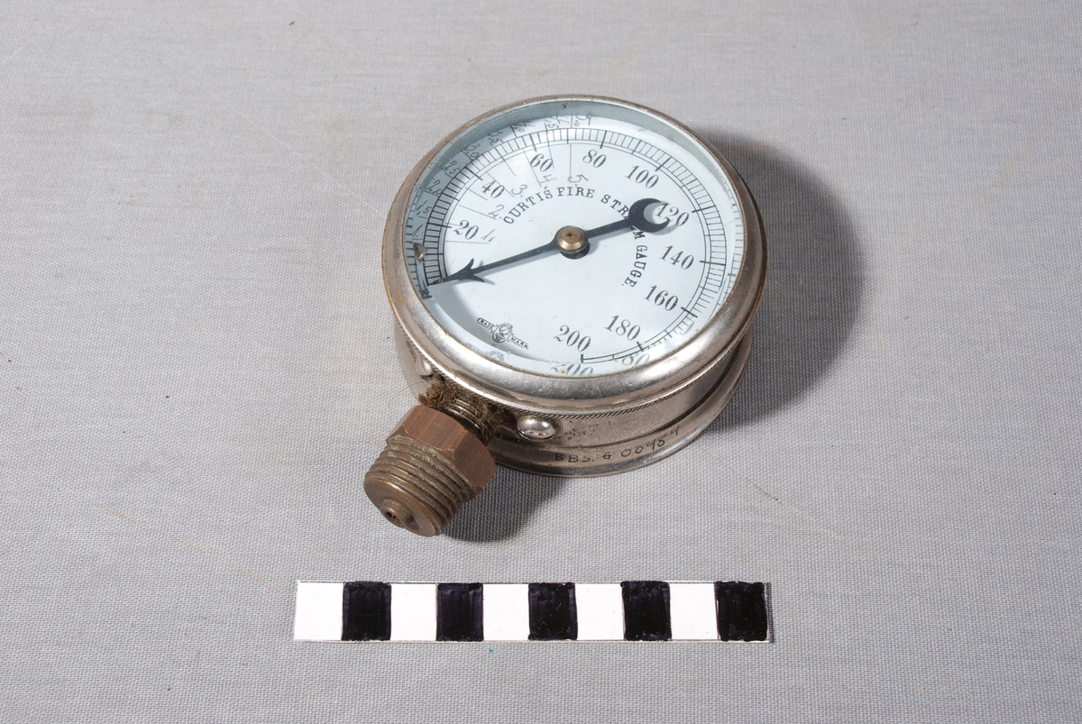 Rund vanntrykksmåler med viser og tallmarkeringer fra 0 til 200. glass på utsiden. På baksiden dreibar måleskive i metall. Koblingsstykke med gjenger i nedkant av instrumentet.