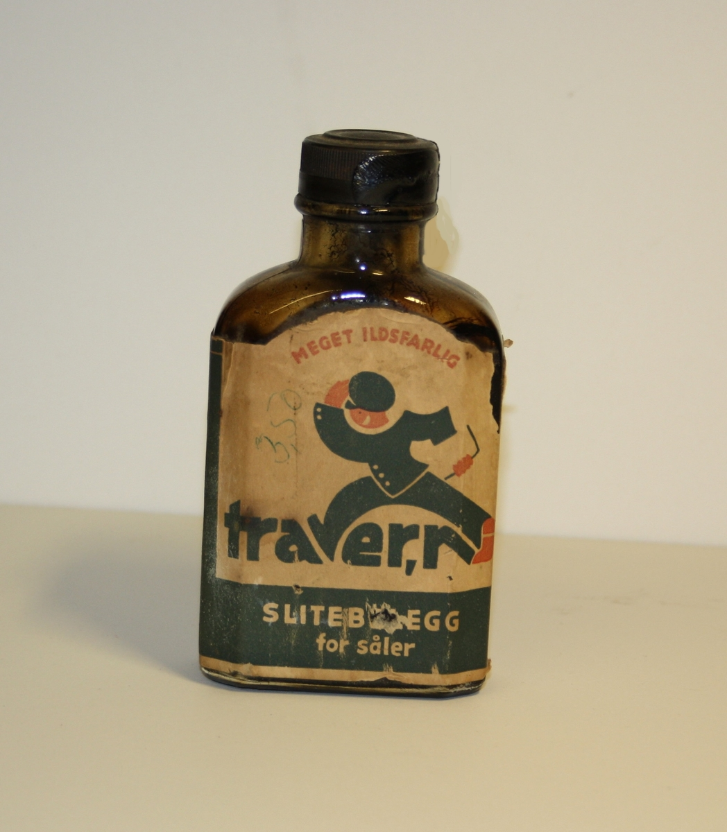 Form: Lita flat flaske med skrukork og pålimt etikett.