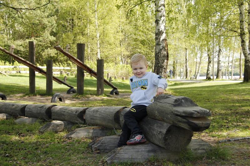 Liten gutt sitter på tømmer i lekeparken på Fetsund lenser (Foto/Photo)