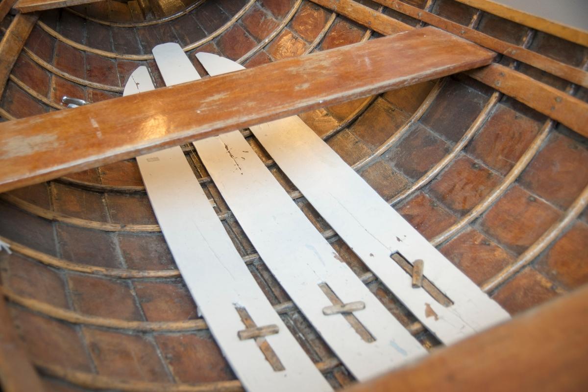 Jolle av tre. Klinbygd med ribber - mahogny. Seks borganger. To tofter, en hvit tilje.