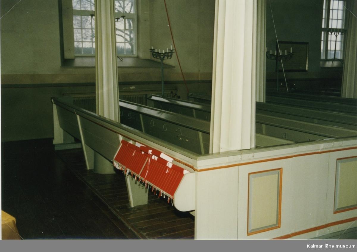 Kyrkbänkarna och kolonnerna som bär upp orgelläktaren i Målilla kyrka.