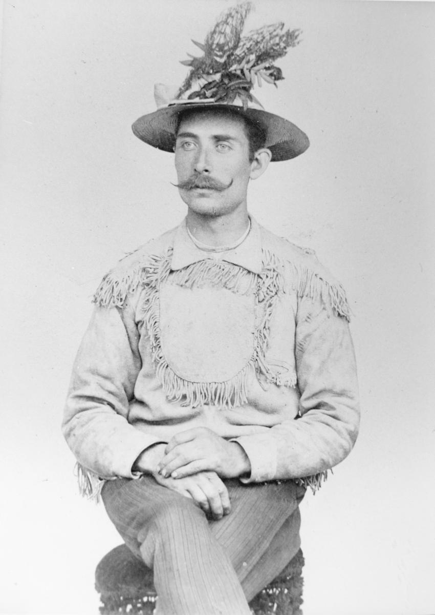 """Selvportrett av Anders Andersson, med kjerringrokk og rogneblader i hatten, og jakke med frynser i """"indianerstil""""."""