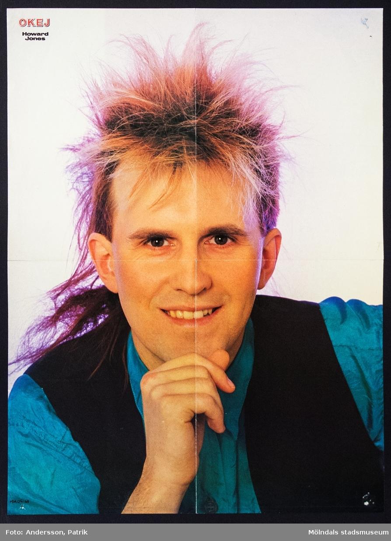 """Poster från tidningen Okej, Nr. 9 1985, pris  11,75 kr.   Postern är dubbelsidig.  På posterns ena sida finns  Howard Jones, brittisk sångare som fick sitt genombrott 1984 med låtarna """"New Song"""", """"What Is Love?"""", """"Hide And Seek"""" och """"Pearl In The Shell"""".   På andra sidan av postern finns: Kiss, en amerikansk rockgrupp som fick sitt stora genombrott i mitten av 1970-talet och är fortfarande aktiva idag.  Tidningen Okej var en poptidning som gavs ut första gången 1980. Den gjorde succé under 1980-talet och räknas som Sveriges största poptidning. Det som gjorde tidningen speciell var blandningen mellan hårdrock och svensk popmusik. Både killar och tjejer läste tidningen. Sista nummret av tidningen Okej gavs ut 2010."""