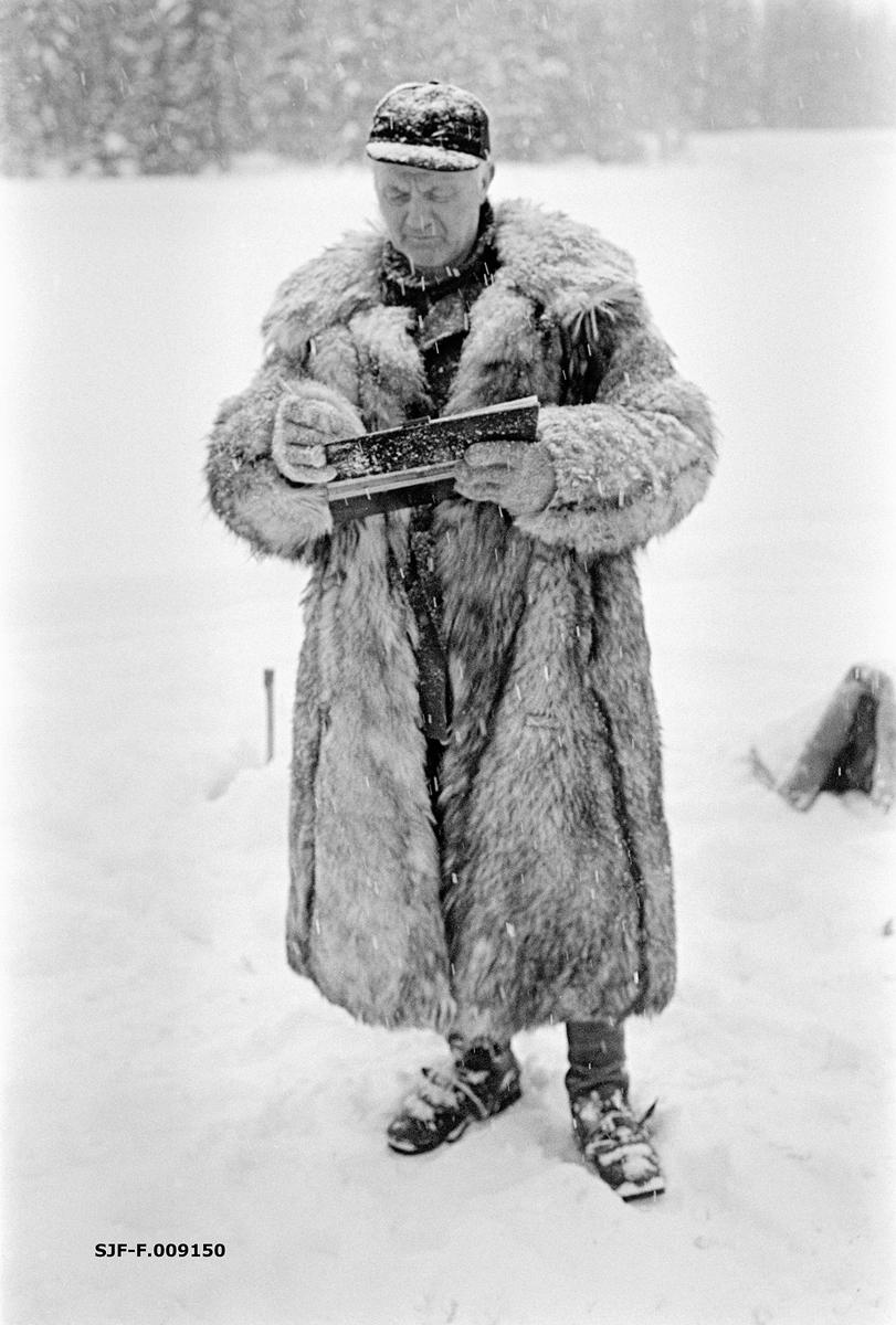 Tømmermåling i Nordre Osen (Åmot kommune i Hedmark) i februar 1980.  Fotografiet viser en mann, kledd i ulveskinnspels og med skjoldlue på hodet, med ei stikkbok i hendene framfor seg.  Stikkboka var «notatblokken» der lengde- og diameter på innmålte tømmerstokker ble loggført, med sikte på forestående avregninger mellom tømmerkjøper og skogeier.  Ulveskinnspelsen holdt varmen i måleren under et forholdsvis stillestående arbeid.  Fra gammelt av var det dessuten vanlig av sagbrukenes og treforedlingsbedriftenes målere også var tømmerbetingere, som inngikk kjøpsavtaler.  I sike sammenhenger gjorde de fine kjørepelsene, som ikke var hver manns eiendom, et inntrykk av økonomisk soliditet som skapte tillit i transaksjonene.  Fotografiet er tatt i forbindelse med opptakene til fjernsynsfilmen «Fra tømmerskog og ljorekoie», som ble vist på NRK 1. mai 1981.  Ettersom poenget med denne filmen var å synliggjøre strevet i tømmerskogen i den førmekaniserte driftsfasen, viser den driftsprosedyrer og redskap som bare noen få veteraner fortsatt brukte på opptakstidspunktet.  I 1980 var størstedelen av tømmertransporten egentlig flyttet fra vassdrag til veg, og mesteparten av målinga var samtidig flyttet til kjøpernes tømmertomter.  Dette fotografiet må derfor oppfattes som en rekonstruksjon fra en virkelighet som tidsmessig sett lå minst en generasjon forut for opptaket.