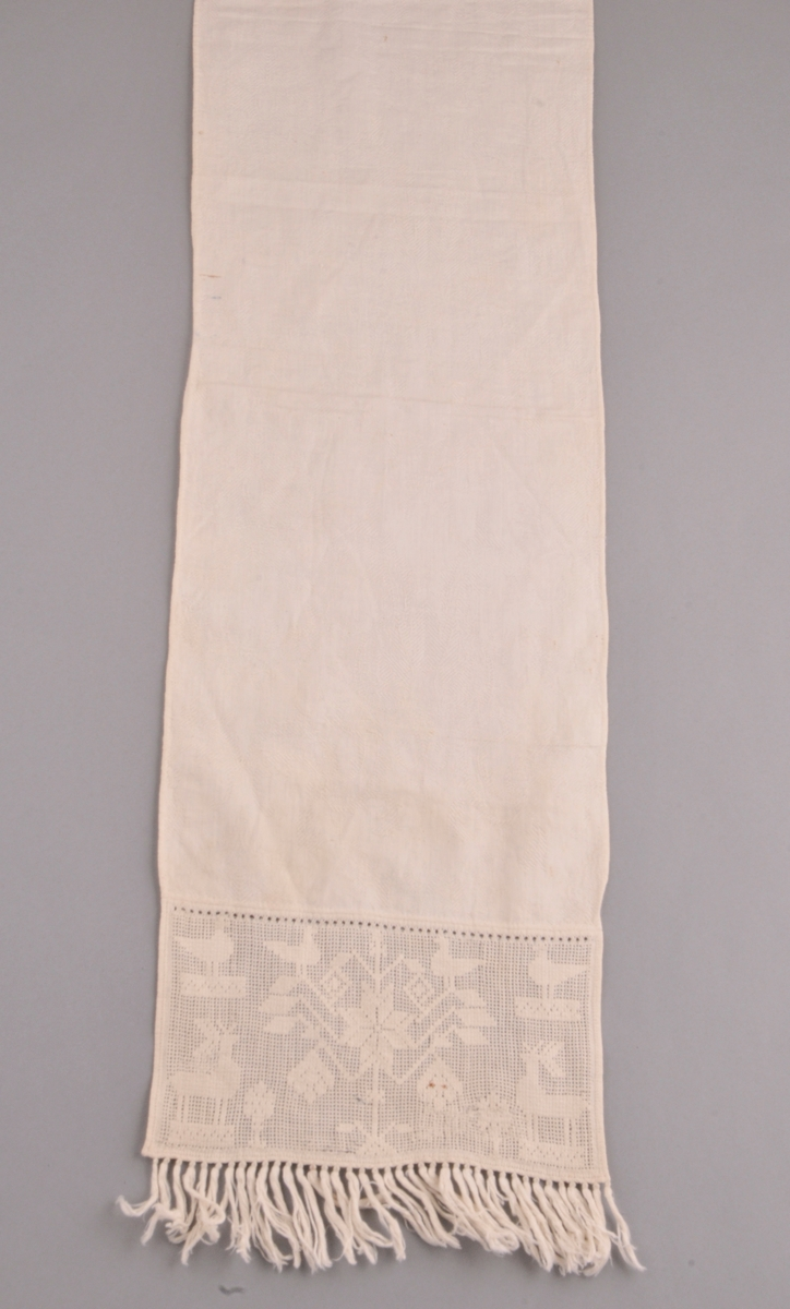 Kvitt klede av bomullstoff, fint falda kring alle kantane med små faldesting og smal fald. Dekor i uttrekkssaum med hjortar, fruktbarhetstre, mjuruspjell, firkantar, frukt m.m.