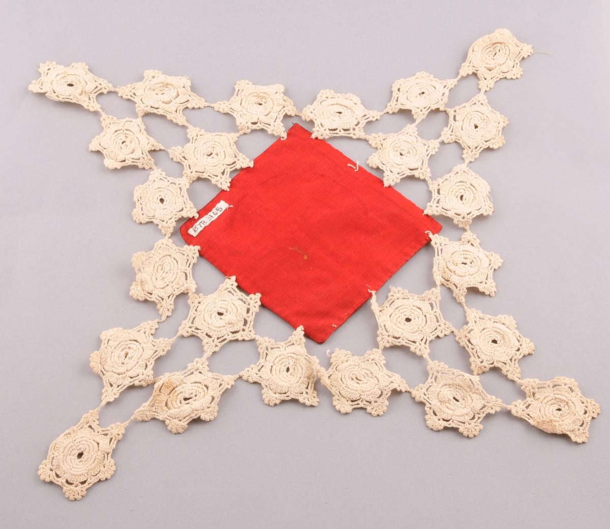 Kvadratisk tekstil sett saman av ein lapp av fløyel, med bakstykke av kypervove raudt stoff, og ei hekla blonde rundt kanten.