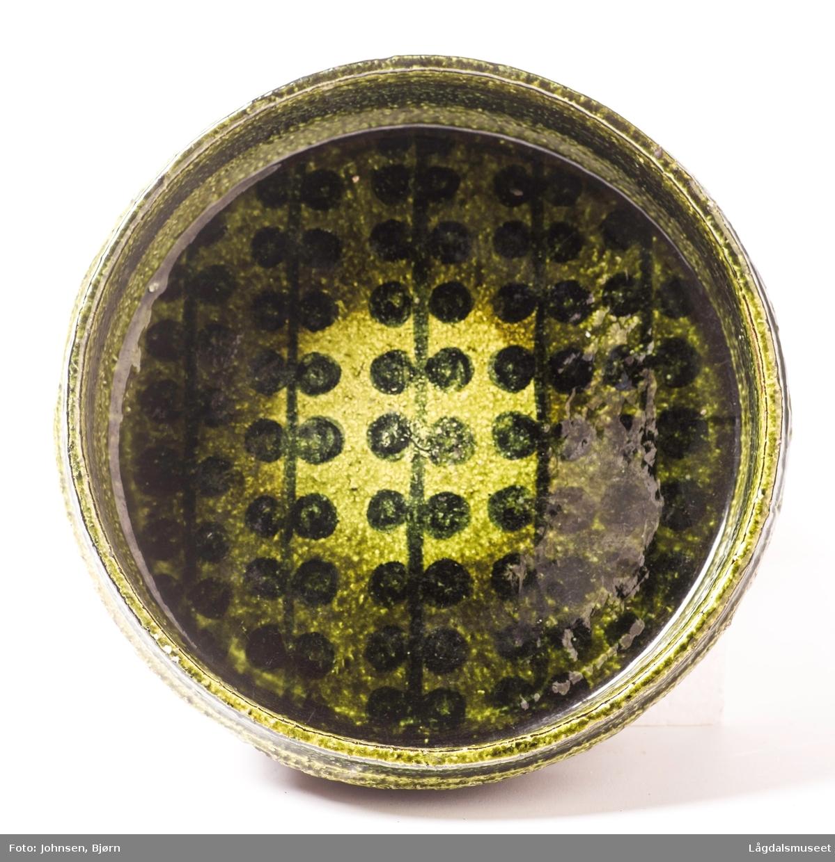 Olivengrønn skål med ornamenter inni.