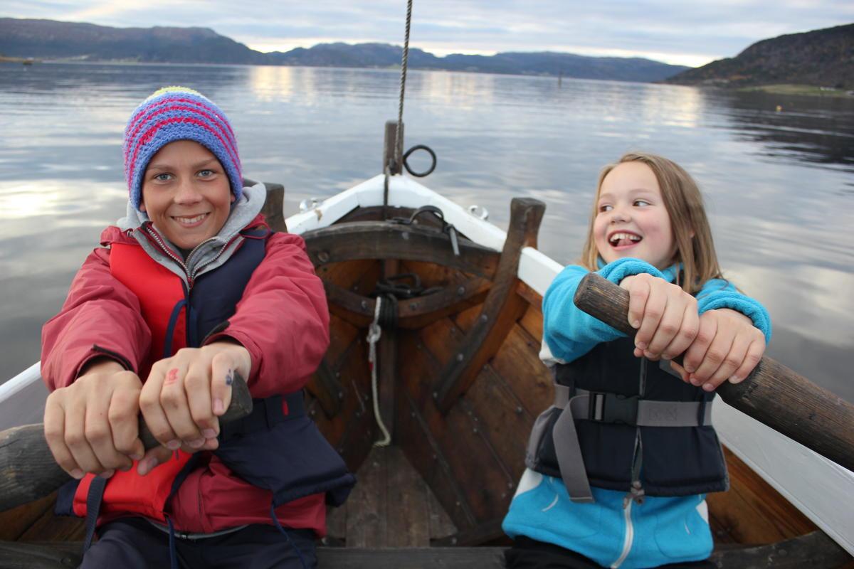 to barn sitter og ror med hver sin åre i en trebåt.