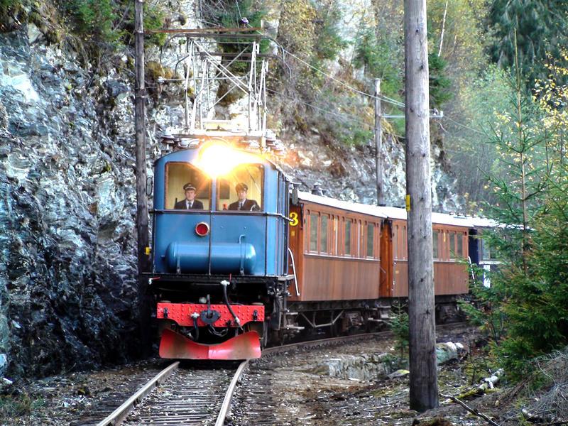 blått lokomotiv og vogner i tre kommer mot på skinnegangen,