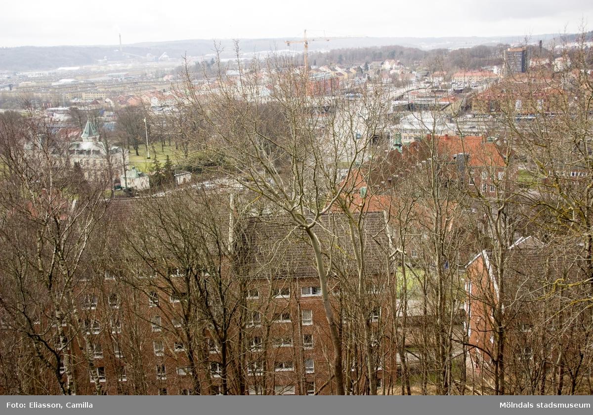 """Vy från Störtfjället över stora delar av centrala Mölndal. Närmast i bild ligger bostadsområdet Silverskatten i rött tegel. Bakom detta, snett ovan till höger, ligger Kvarnbyskolan. Till vänster i bild ser man det pampiga """"slottet"""" som en gång i tiden var Papyrus disponentvilla, idag förvaltat av företaget Forever Living. I fonden till vänster ligger Åbyområdets lägenheter i gult tegel. Den skogsbeklädda kullen bakom höghuset på Storgatan är Åbykullen."""